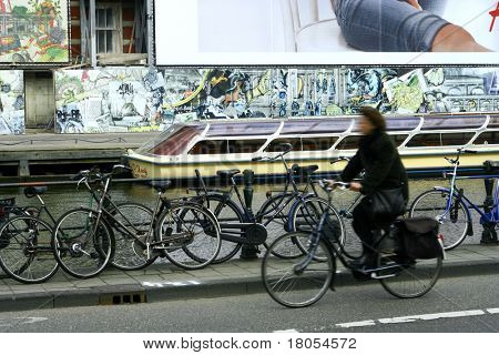 Two world:Concept of slowing down - A lady on her bike rushing past a parked boat in the canal