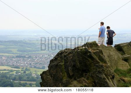 Two men reaching the highest point of a peak, looking at the vast valley below