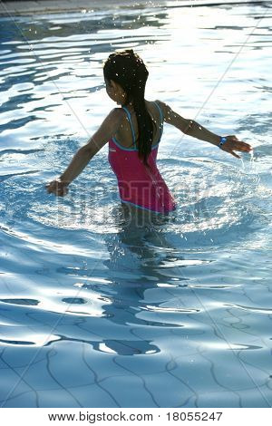 A girl wades gently into the swimming pool in early evening