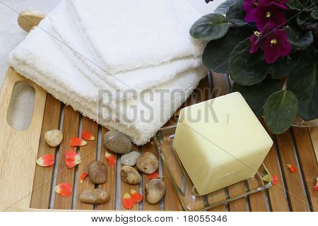 A setting for a spa beauty treatment consisting of a bowl of floral scented water and pebbles for stone therapy