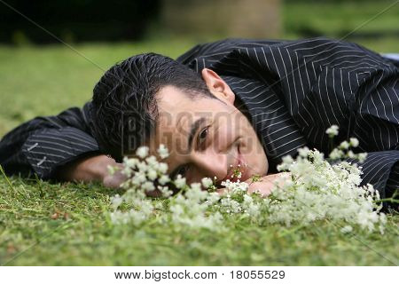 A young man laying down in field of flowers, in touch with his feelings and emotion.
