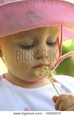 A beautiful baby girl curious with the  'honesty' seedhead.Concept: Young and curious