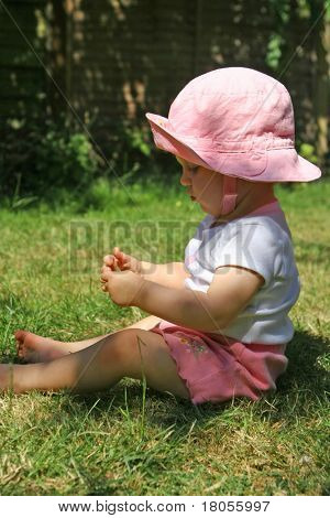 A curious baby girl studying some grass she has just picked up Concept:Growing curiosity