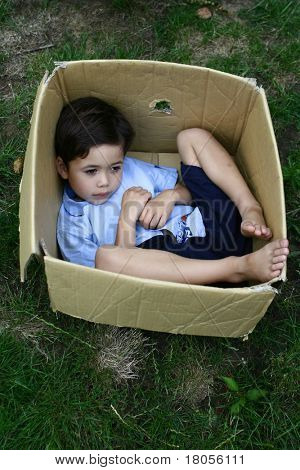 A boy plays hide and seek in a cardboard box. Concept : Grow and evolve