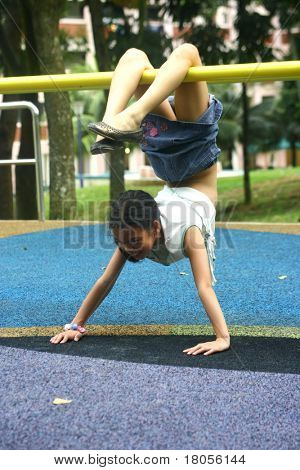 Concept: Hang on. A young girl hangs upside down on a playground bar, balancing as not to fall off