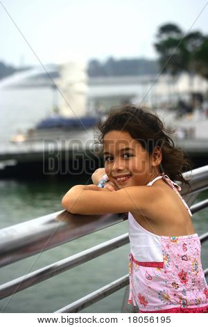 A young girl posing by the bar, overlooking the Merlion, Singapore