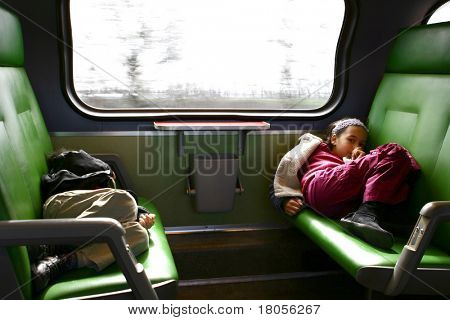 A young girl and her little brother got a little bored on her journey in the fast moving train