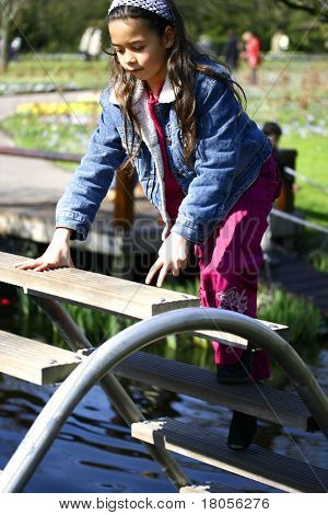 A young girl climbs on a curved steps across a river, being careful not to slip
