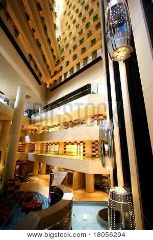 A grand lobby of a high rise building with two moving internal elevator
