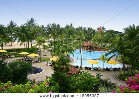 View of the sprawling blue swimming pool by a hotel in the tropcs