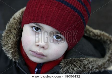 A boy feeling cold as he went out for a walk in winter, completes with hat, scarf and a winter coat