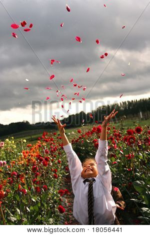 A young girl throws a bunch of dahlia petals in the air, in a flower farm