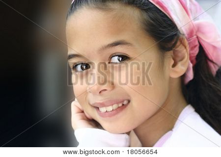 A girl with brown eyes and pink bandanna enjoying the outdoor.