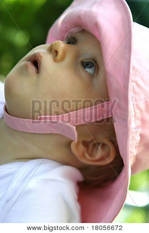 Beautiful baby girl in pink hat mesmerized by the sound of rustling of leaves in the trees.