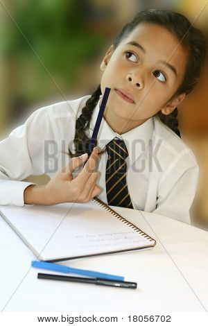 A young girl student thinking hard as she attempts at her homework.