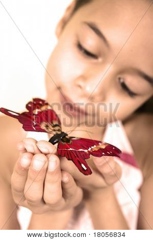 A young girl admires a red butterfly landing on the tip of her finger.