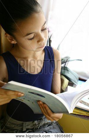 Una niña absorber en su libro, bellamente iluminada por la luz de la ventana.
