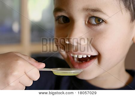 A young boy about to have his medicine in a spoon.