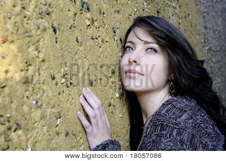 A beautiful young woman with clear blue eyes and long dark hair, leaning against a textured wall looking up into the sky.