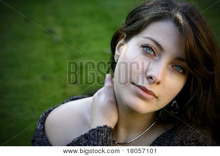 Sultry dark haired woman with clear blue eyes enjoying the fresh outdoors.