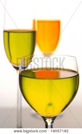 Three glasses of exotic concoction in tall glasses against white backlighting.