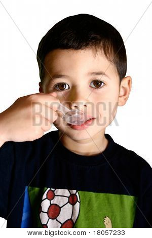 A young boy taking his cough syrup from a spoon, isolated on white background.