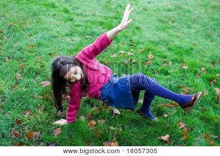 A young girl slips over on very wet grass.