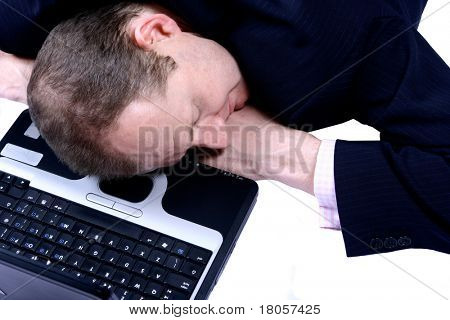 A businessman fallen asleep on his laptop, over white.