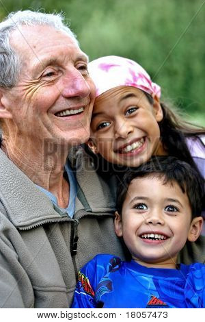A young boy and his sister enjoying special times spent with their grandfather. Concept of love, togetherness, tenderness and family value.
