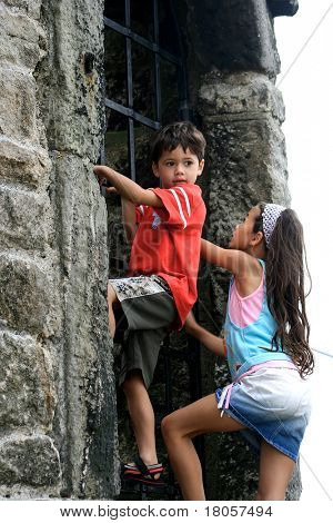 A little boy and his sister attempts at climbing an old castle ruin gate.Concept : Fear and development