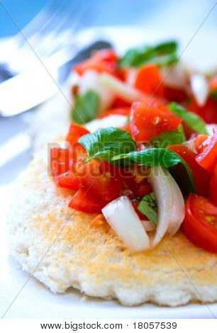 Plum tomato salad, onion and basil served on toasted slices of bread.