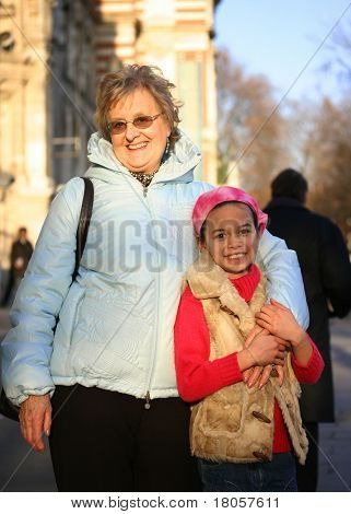 A young girl with her loving grandmother, outdoors.