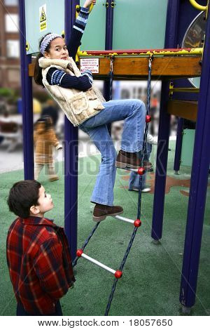 A young girl climbs on the ladder to a playground structure, watched by her younger brother
