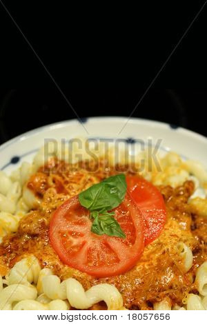 A plate of tasty tomato pasta with sliced beef tomatos and sprig of basil against black