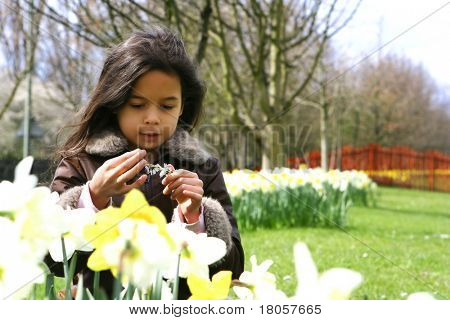 A young girl appreciating the beauty of daisy chains, surrounded by beautiful daffodils in springtime.
