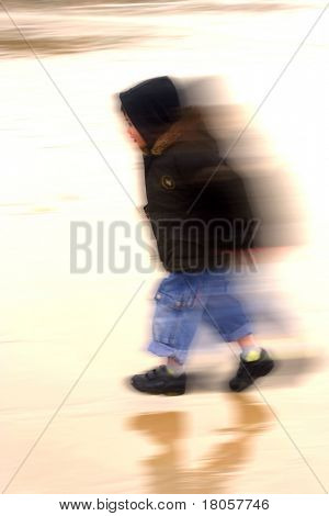 A young boy running along the cold, wet beach in winter, showing movement blur digitally rendered.