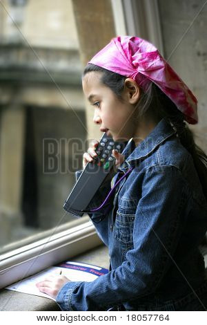 A young girl listening to the narrator over the mobile device when visiting historic Bath, England.