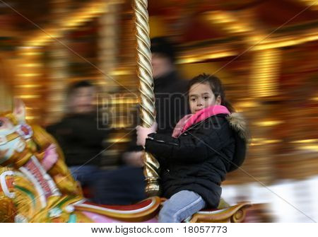 A young girl enjoying her ride on the wooden carousel at an amusement fair showing lots of movement
