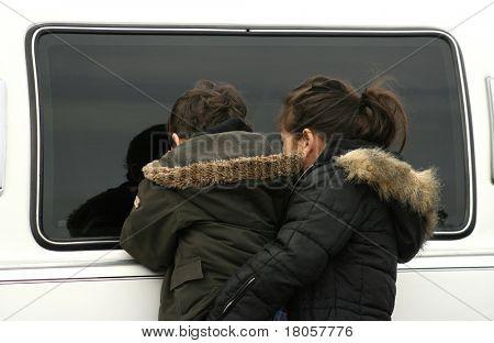 Una niña ayudando a su hermano curioso hasta en la mirada furtiva en la ventana de una limusina