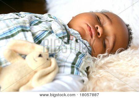 Bela criança de parentesco mistura dormindo pacificamente no tapete de pele de carneiro, acompanhado de sua bu fofo