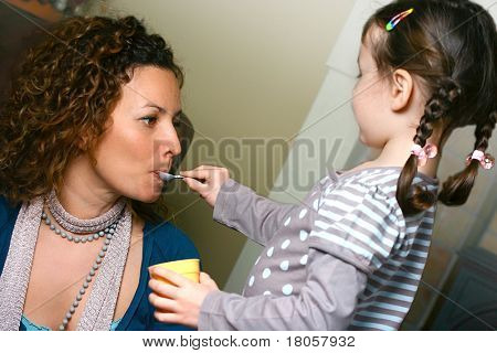 A little girl pretending to feed her mom with her plastic toy spoon.