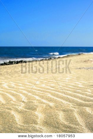 Rippled sand on a golden sandy beach with vast blue,cloudless sky.