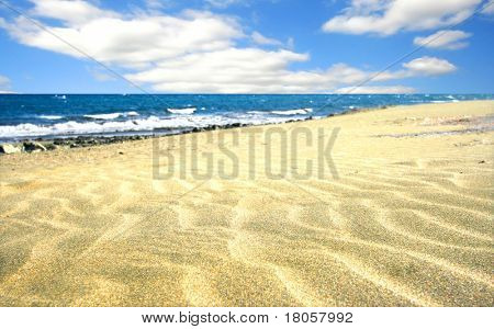 Beach with soft sand, rippled texture of windblown effect, vast blue sea with cloudless sky. Focus is on sand in foreground.