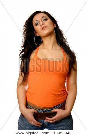 Beautiful Italian model in orange tank top and casual jeans, fingers resting on wide leather belt, isolated on white.