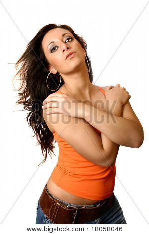 Beautiful Italian model in orange tank top and casual jeans, hands resting on shoulder, isolated on white.