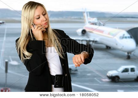 Caucasian businesswoman looking at her watch,  in the departure hall of an airport, waiting to catch her flight for her business travel. Concept of business air travel and time pressure.