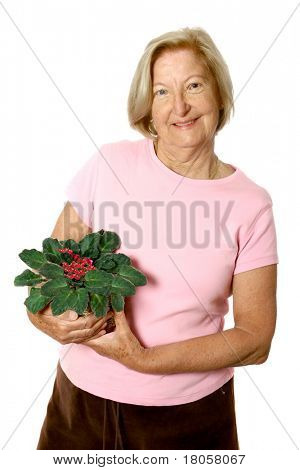 Happy mature caucasian female in casual outfit, holding a pot of '' African violet '' a type of houseplant, isolated on white.
