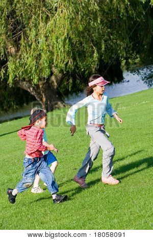 Young children having fun playing chase in the park on a lovely summer's afternoon.