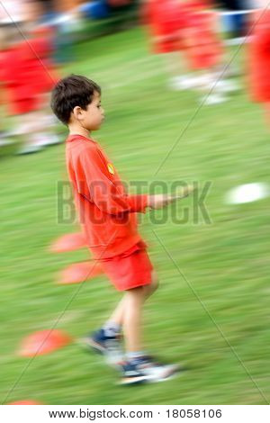 Young boy walking quickly towards his team with a spoon and a potato, taking part in the school's sport's day, showing movement.