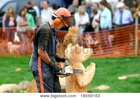 Master woodcarver finishing off his bear wood carving done with a chainsaw.